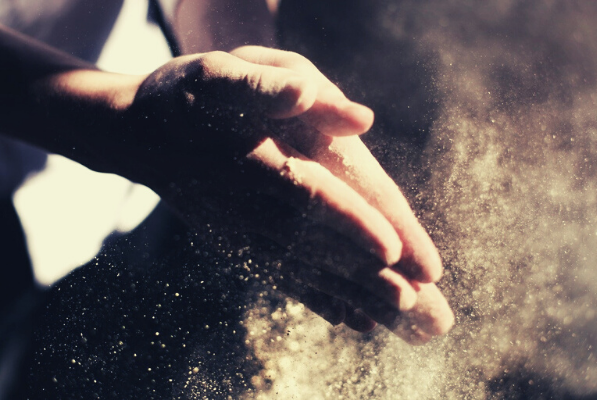Persons' hands clapping dust away